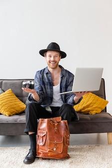 Uomo di smiley pieno colpo che tiene macchina fotografica e computer portatile