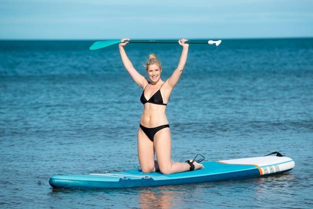 Donna sorridente a tutto campo che fa paddleboarding