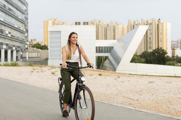 Donna piena di smiley colpo in sella alla sua bici