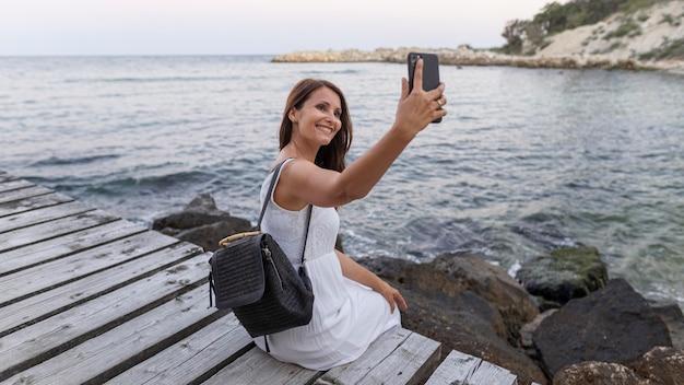 Donna di smiley pieno colpo prendendo selfie