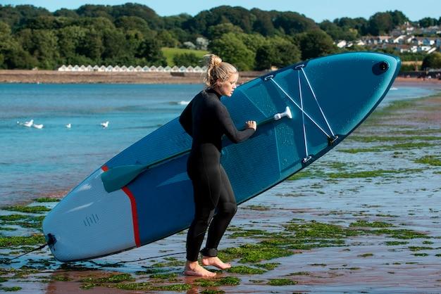 Donna a tutto campo che trasporta il paddleboard