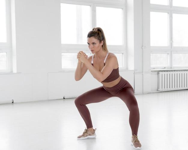 Colpo completo della donna che fa le esercitazioni