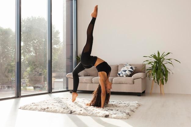 Donna piena del colpo che fa yoga a casa