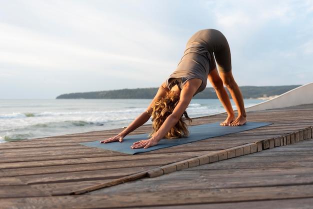 Donna piena del colpo che fa yoga vicino al mare