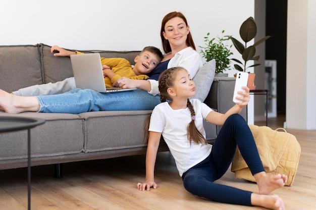 Donna e bambini a tutto campo con dispositivi