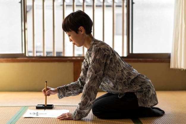 Donna del colpo pieno che dipinge lettere giapponesi