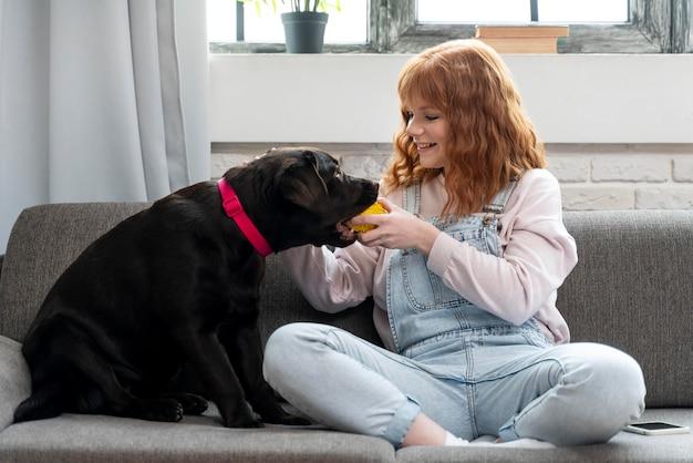 Donna piena del colpo che gioca con il cane sul divano