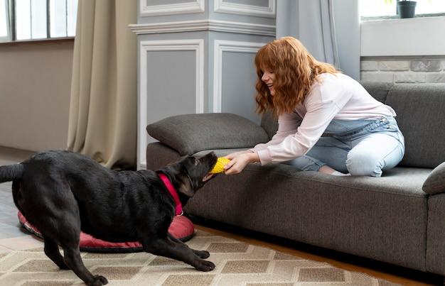 Donna piena del colpo che gioca con il cane a casa