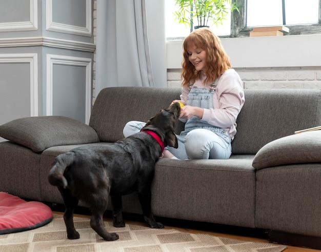 Donna piena del colpo che gioca con il cane al chiuso