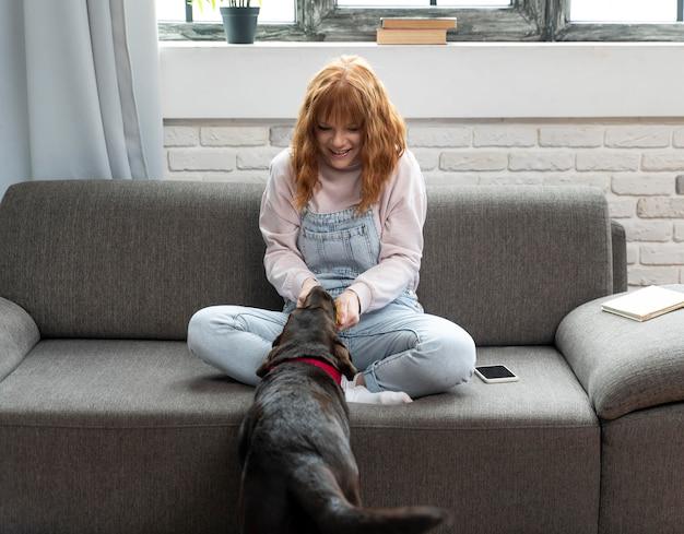 Donna piena del colpo che gioca con il cane