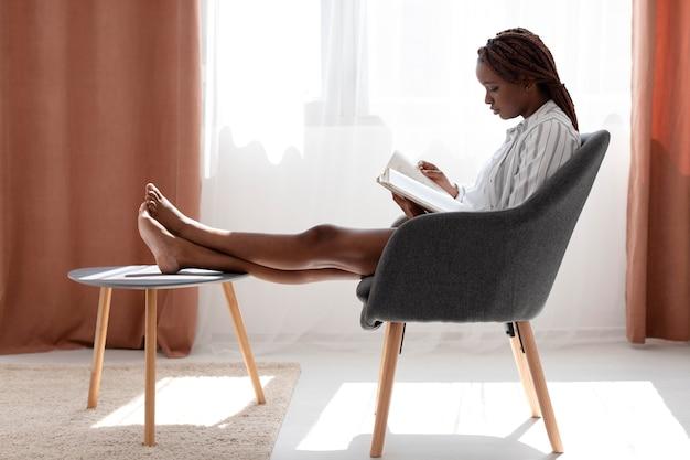 Donna a tutto campo che legge sulla sedia