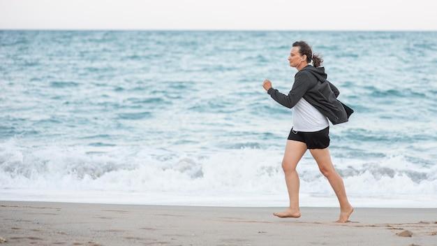 Donna piena del colpo che funziona sulla spiaggia