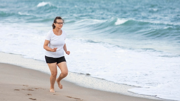 Donna piena del colpo che funziona sulla riva