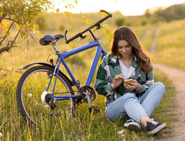 Donna a tutto campo seduta sull'erba