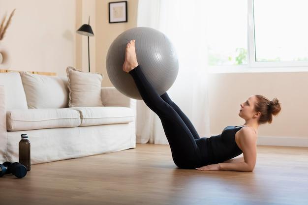Donna a tutto campo che si allena con la palla da ginnastica a casa