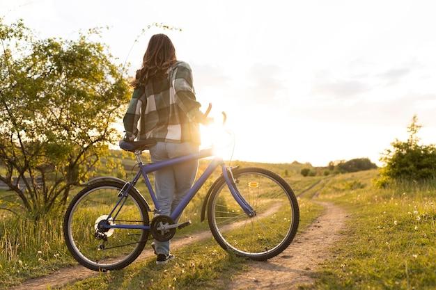 Donna a tutto campo con la bicicletta all'aperto