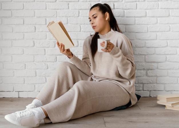 Donna piena del colpo con il libro e la tazza sul pavimento