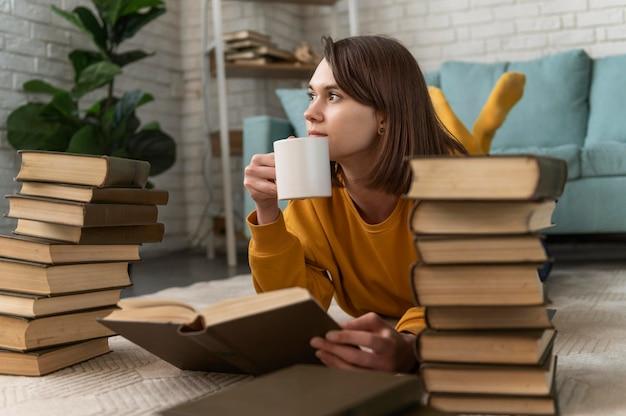 Donna piena del colpo con tazza e libri