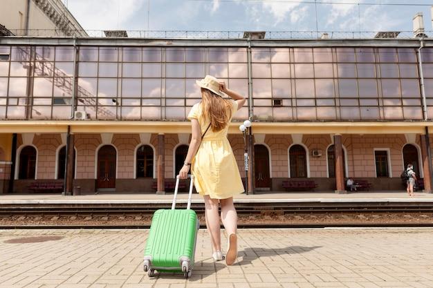 Donna della foto a figura intera con bagagli verdi