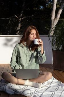 Donna piena del colpo con il computer portatile all'aperto
