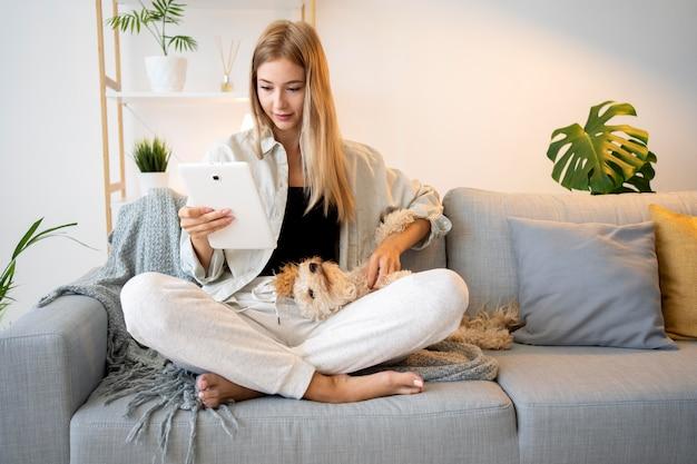 Donna a tutto campo con tablet e cane