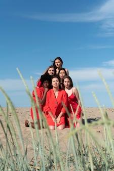 Donne a tutto campo in posa in spiaggia