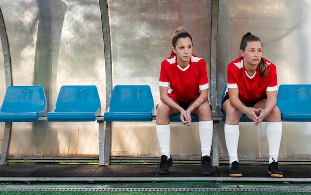Donne del colpo pieno che si siedono sulle sedie