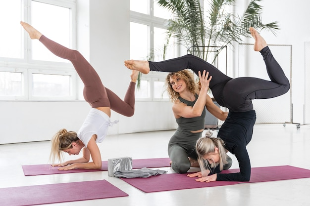 Insegnante di yoga del colpo completo che aiuta la donna