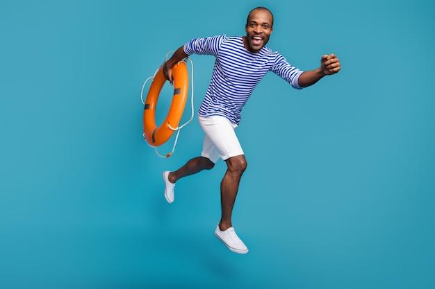 A grandezza naturale del ragazzo soccorritore marinaio salta portare salvagente in gomma correre fretta corsa
