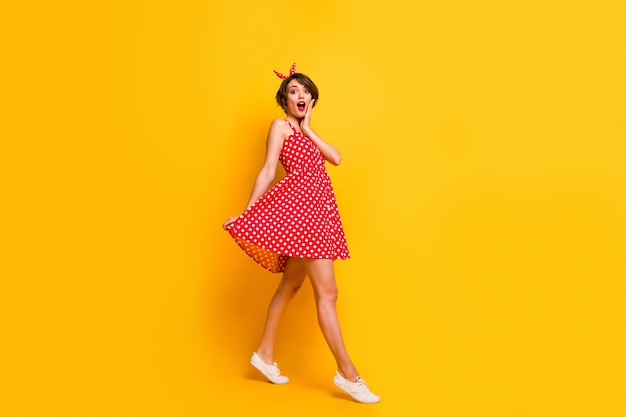 Foto a grandezza naturale della ragazza stupita a piedi vai a vedere un incredibile venerdì nero affare colpito urlo toccare le mani faccia indossare un bell'aspetto vestiti isolati sopra la parete di colore brillante