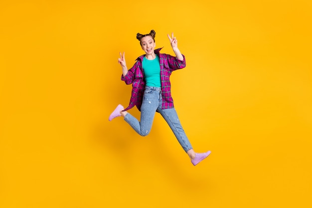 Foto a grandezza naturale di una donna attraente che salta mostra i simboli del segno v saluta gli amici che si incontrano dopo l'autoisolamento indossa una camicia a quadri magenta casual jeans scarpe da ginnastica isolate giallo vivido sfondo di colore