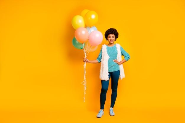 Foto a grandezza naturale della ragazza afroamericana allegra tenere i baloons d'aria che ottiene in occasione dell'anniversario indossare scarpe alla moda bianche blu vestito lanuginoso alla moda isolate sopra la parete di colore giallo