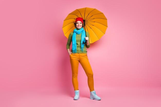 Foto a grandezza naturale della ragazza allegra che tiene il suo ombrellone giallo brillante goditi il viaggio nel tempo libero della stagione indossare pantaloni jumper scarpe isolate su un muro di colore rosa