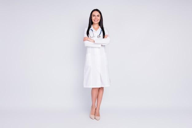 La foto a grandezza naturale della signora allegra con le braccia incrociate indossa lo stetoscopio del camice da laboratorio bianco
