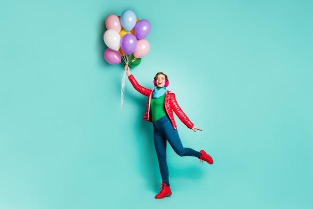 La foto a grandezza naturale della ragazza adorabile allegra tiene molte palline di elio d'aria che volano nel cielo indossano stivali rosa alla moda con un maglione verde autunno isolato su un muro di colore turchese