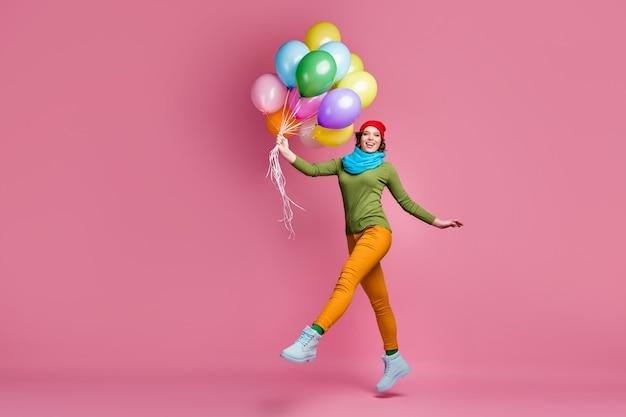 Foto a grandezza naturale allegra bella ragazza salta tenere molti baloons d'aria che ottiene in occasione di festa godersi l'autunno tempo libero indossare pullover rosso copricapo pantaloni isolato muro di colore rosa