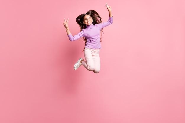 La foto a grandezza naturale di una ragazzina allegra che salta fa indossare un maglione viola con il segno v isolato su uno sfondo di colore pastello