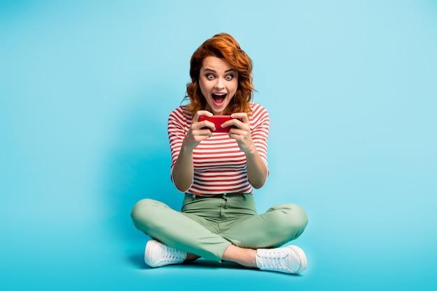 Foto a grandezza naturale di donna funky pazza seduta sul pavimento leggi notizie sui social media urlo impressionato wow omg indossare scarpe da ginnastica maglione bianco verde isolate su colore blu