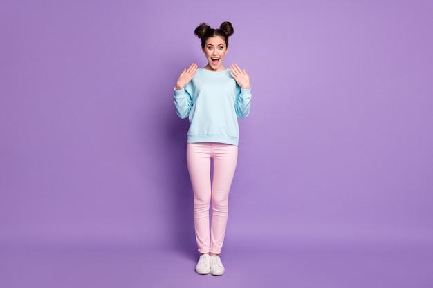 Foto a grandezza naturale di una ragazza pazza positiva allegra stupita che sente una meravigliosa novità impressionata urlare indossare scarpe maglione rosa isolate su uno sfondo di colore viola