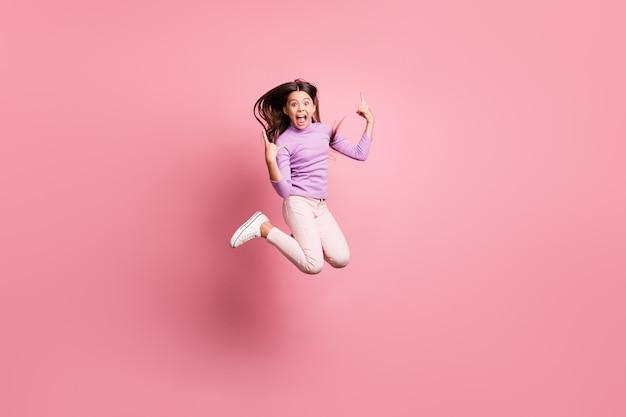 Foto a grandezza naturale di una ragazzina pazza che salta mostra il simbolo delle corna indossa un maglione viola isolato su uno sfondo di colore pastello