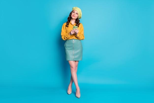 Foto a grandezza naturale di una curiosa studentessa blogger goditi il riposo rilassati usa il cellulare guarda copyspace pensa pensieri social media post indossare copricapo giallo tacchi a spillo isolati colore blu sfondo