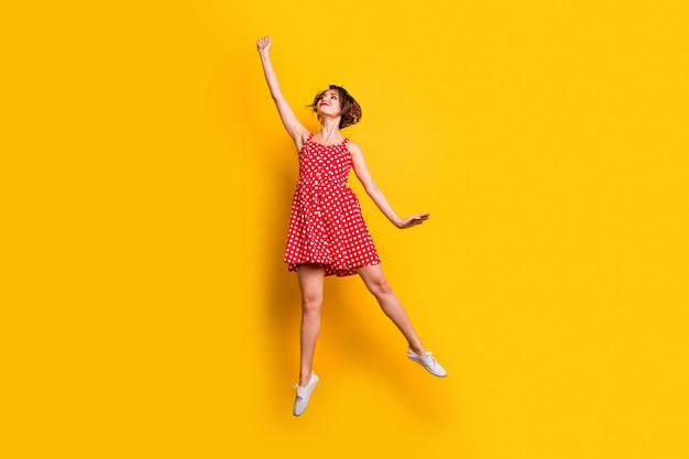 Foto a grandezza naturale di carina ragazza carina allegra salta tenere la mano vuole catturare l'ombrellone volante indossare un bell'aspetto scarpe gonna stile vintage isolate su muro di colore giallo