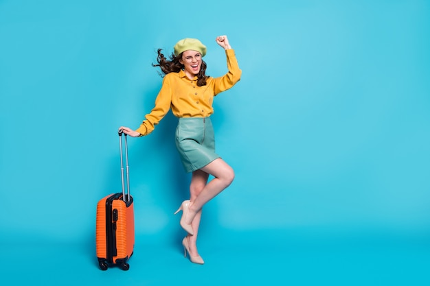 Foto a grandezza naturale della ragazza estatica vincere il tour della lotteria del fine settimana alzare i pugni urlare tenere la valigia indossare stile elegante alla moda camicetta gialla tacchi a spillo isolati su sfondo blu