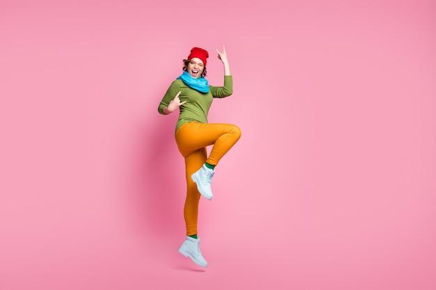 Foto a grandezza naturale ragazza energica salta goditi rallegrati vendite primaverili concerto rock and roll rendere il simbolo cornuto urlo indossare rosso blu giallo verde scarpe pantaloni copricapo isolato muro di colore rosa