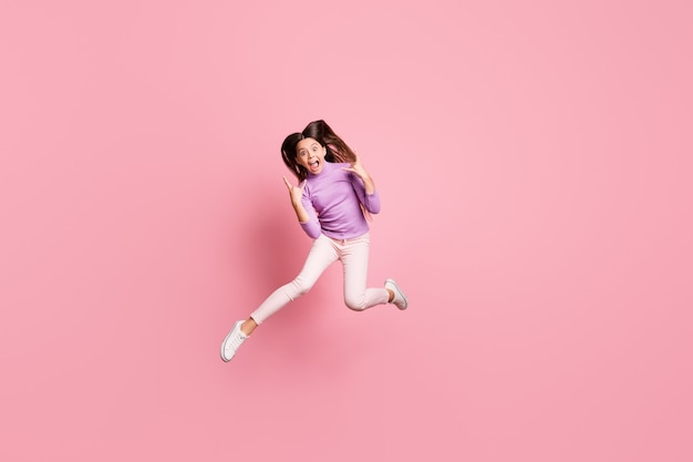 La foto a grandezza naturale di una ragazzina eccitata che salta fa in modo che il segno v indossa un maglione viola isolato su uno sfondo di colore pastello