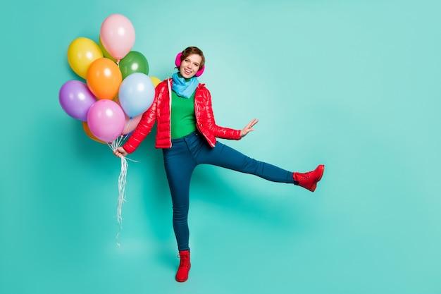 Foto a grandezza naturale di una donna divertente ed energica che porta molti palloncini colorati agli studenti che indossano una festa casual sciarpa del cappotto rosso rosa paraorecchie pantaloni scarpe isolate muro color verde acqua