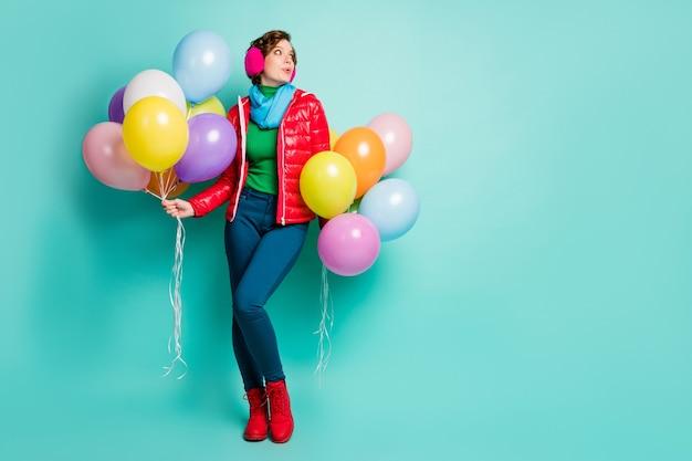 Foto a grandezza naturale di una signora divertente che tiene molte mongolfiere colorate studenti festa guardare spazio vuoto indossare casual cappotto rosso sciarpa rosa orecchio copre pantaloni scarpe isolato verde acqua muro