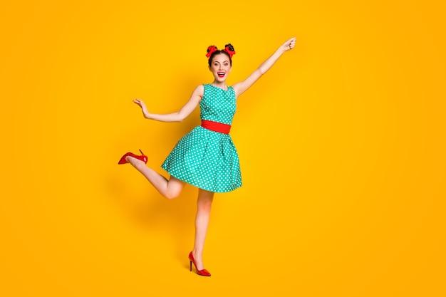Foto a grandezza naturale della ragazza che tiene la mano indossando abiti stile di vita turchesi isolati su uno sfondo di colore brillante