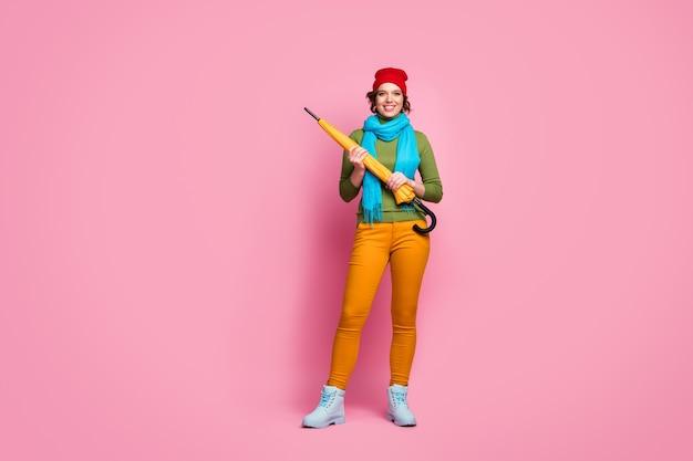 Foto a grandezza naturale di una bella ragazza sognante che tiene un ombrello luminoso per godersi il tempo piovoso tempo libero a piedi indossare un vestito stile casual isolato su un muro di colore rosa