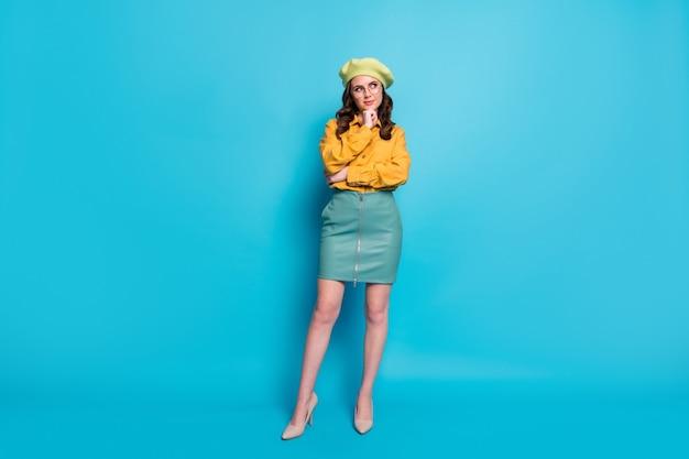 Foto a grandezza naturale di una ragazza con una mentalità che tocca il mento con le dita guarda copyspace pensa pensieri decidono scegliere decisioni scelta indossare copricapo isolato su sfondo di colore blu